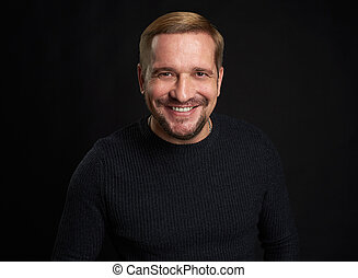 Studio shot of a happy man on black studio background
