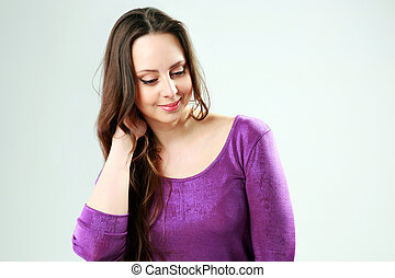 Studio shot of a smiling woman over gray background