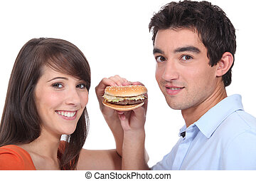 Studio shot of a young couple sharing a hamburger