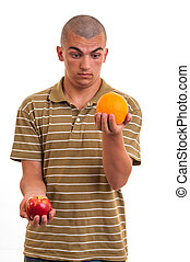 Studio shot of a young man comparing an apple to an orange