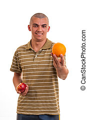 Studio shot of a young man who offers orange instead of red apple, concept of healthy nutrition