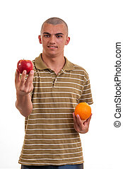 Studio shot of a young man who offers apples instead of orange, concept of healthy nutrition