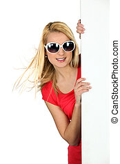 Studio shot of a young woman in sunglasses with a board left blank for your image