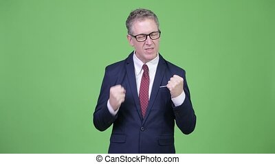 Studio shot of angry mature businessman pulling his hair out...