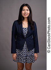Asian woman wearing blue dress and cardigan sweater against gray