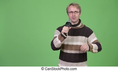 Studio shot of blonde handsome man using microphone and...