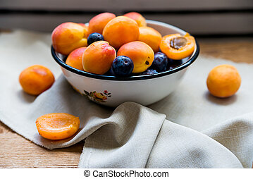 Studio shot of bowl with plums and apricots