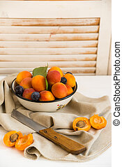 Studio shot of bowl with plums, apricots and knife