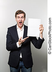 studio shot of businessman with sheet of paper - Blond-...