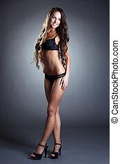 Studio shot of charming woman in black lingerie
