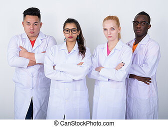 Studio shot of diverse group of multi ethnic doctors with arms c