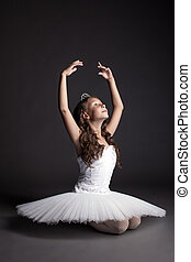 Studio shot of dreamy graceful ballerina, on gray backdrop