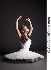 Studio shot of dreamy graceful ballerina, on gray backdrop