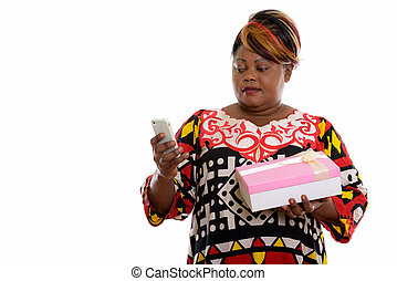 Studio shot of fat black African woman using mobile phone and ho