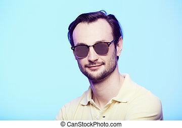Studio shot of handsome man wearing sunglasses over blue background