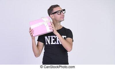 Studio shot of happy nerd man shaking gift box - Studio shot...