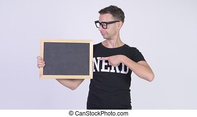 Studio shot of happy nerd man showing blackboard and giving...