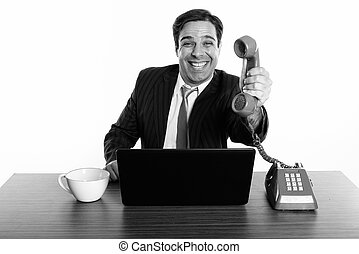 Studio shot of happy Persian businessman smiling while giving old telephone with laptop and coffee cup on wooden table