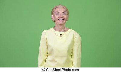 Studio shot of happy senior businesswoman with blond hair -...