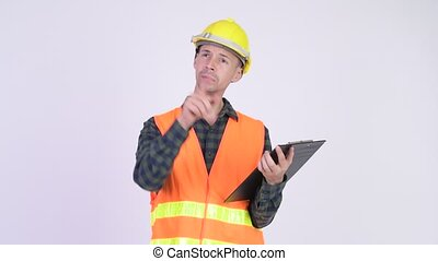 Studio shot of man construction worker holding clipboard and...