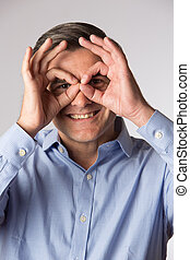 Studio Shot Of Man Making Spectacle Shape With His Hands