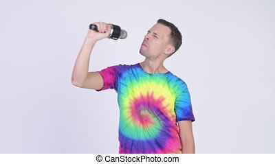 Studio shot of man with tie-dye shirt singing with...