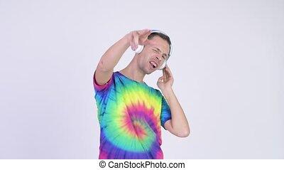 Studio shot of man with tie-dye shirt wearing headphones as...