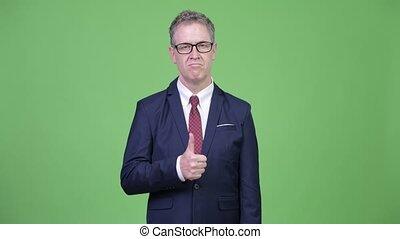 Studio shot of mature businessman giving thumbs up - Studio...