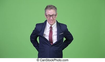 Studio shot of mature businessman looking tired while having back pain