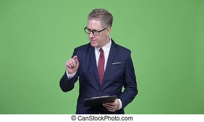 Studio shot of mature businessman reading on clipboard while...
