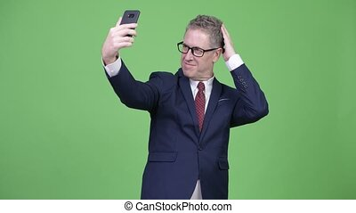 Studio shot of mature businessman taking selfie