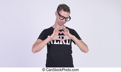 Studio shot of nerd man showing hand heart gesture - Studio...