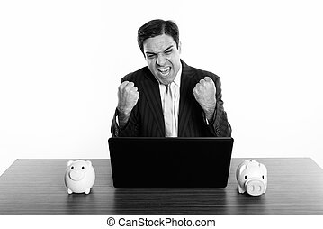 Studio shot of Persian businessman looking excited while using laptop with two piggy banks on wooden table