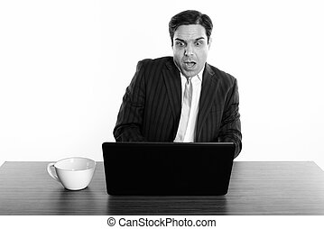 Studio shot of Persian businessman looking shocked while using laptop with coffee cup on wooden table