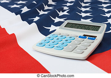 Studio shot of ruffled national flag with calculator over it - United States of America