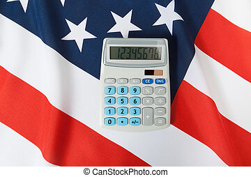 Studio shot of ruffled national flag with calculator over it - United States
