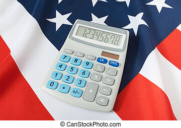 Studio shot of ruffled national flag with calculator over it - USA