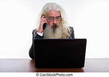 Studio shot of senior bearded businessman talking on mobile phon