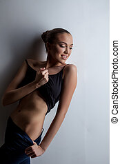 Studio shot of sexy tanned model bared her waist