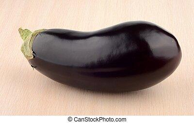 Studio shot of single aubergine eggplant on bright wooden table