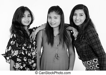 Studio shot of three happy young Persian woman friends smiling while leaning on the shoulder