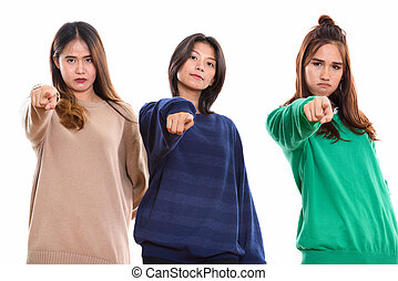Studio shot of three young Asian woman friends pointing finger a