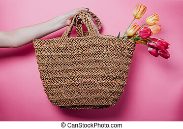 Studio shot of woman holding a straw bag with tulips on pink background. Spring sale in stores. Accessories