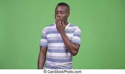 Studio shot of young African man looking guilty - Studio...