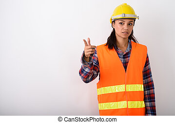 Studio shot of young Asian woman construction worker pointing to