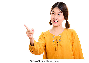 Studio shot of young beautiful Asian woman pointing finger at di