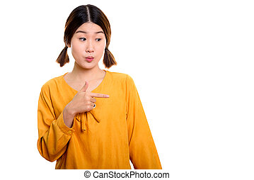 Studio shot of young beautiful Asian woman pointing finger to th