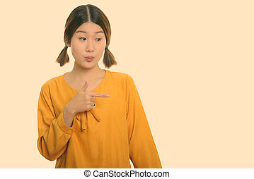 Studio shot of young beautiful Asian woman pointing finger to the side