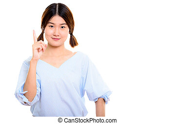 Studio shot of young beautiful Asian woman pointing finger up