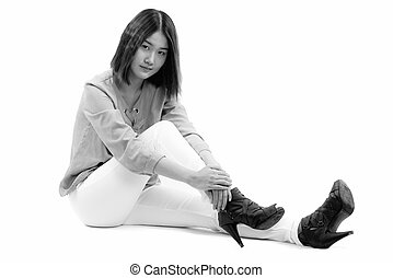 Studio shot of young beautiful Asian woman sitting on the floor